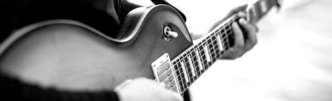 Lehrer spielt E-Gitarre - Detailaufnahme